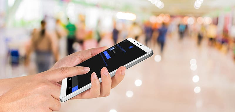 male hand is holding a modern touch screen phone and Blurred image of people walking at shopping mall , blur background with bokeh
