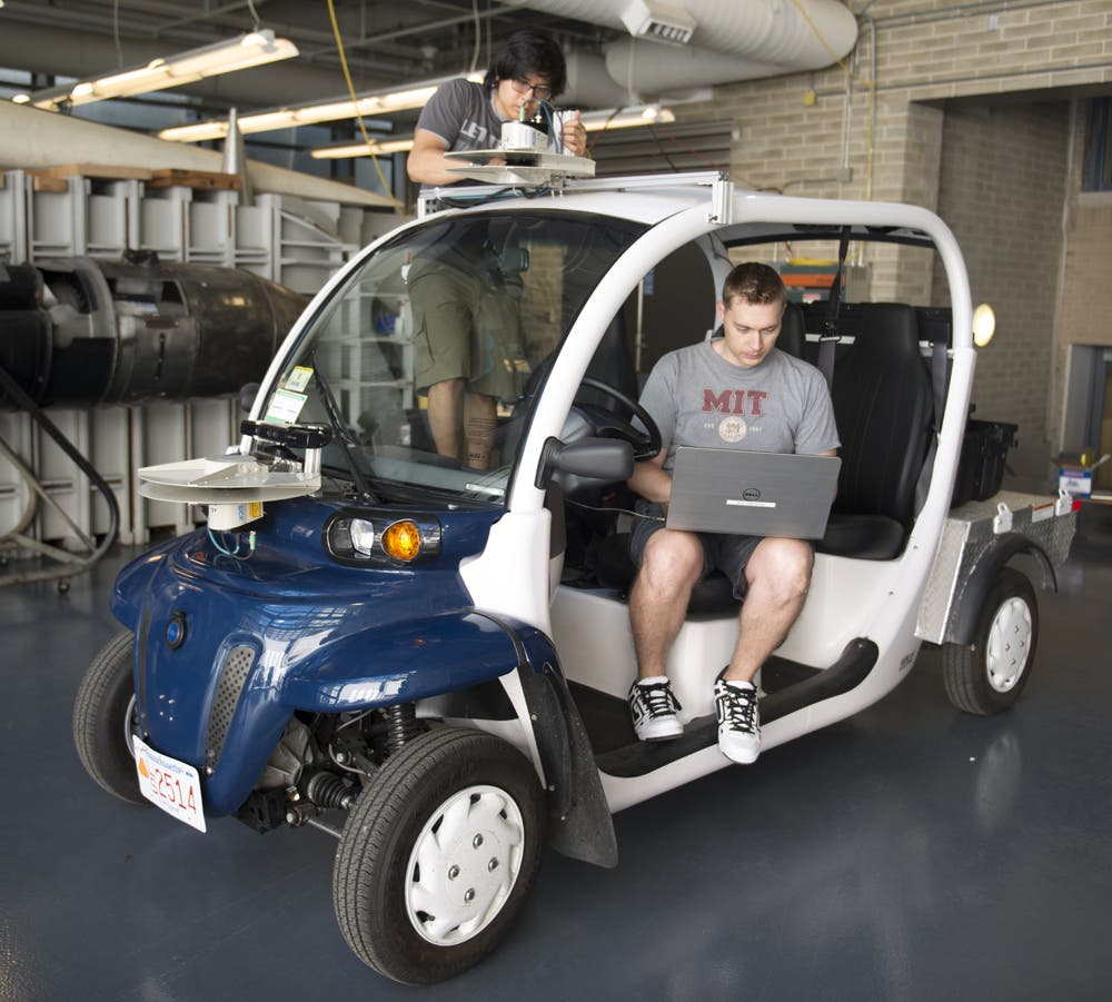 Justin Miller und Wally Wibowo vom Aerospace Controls Lab arbeiten an einem der Fahrzeuge. - Graduate student Justin Miller and undergrad Wally Wibowo of the Aerospace Controls Lab working on vehicles outfitted with sensors that match those of self-driving cars. This work is part of the Ford-MIT Alliance and aims to predict pedestrian behaviors on short time-scales while also providing data to support a mobility-on-demand system for the MIT campus.